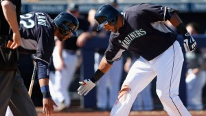 PEORIA, AZ - MARCH 05:  Nelson Cruz #23 (R) of the Seattle Mariners low fives Robinson Cano #22 at home plate after Cruz hit a two run home-run against the San Diego Padres during the third inning of the spring training game at Peoria Stadium on March 5, 2015 in Peoria, Arizona.  (Photo by Christian Petersen/Getty Images)