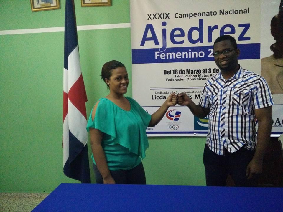 Carlos del Rosario directivo de la Federación Dominicana deAajedrez felicita a la campeona nacional de ajedrez femenino Wilsaida Díaz.