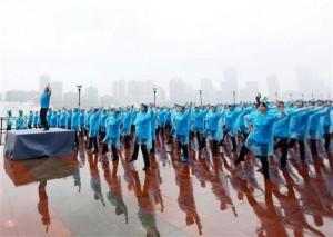 En esta imagen, tomada el 21 de mayo de 2016, mujeres equipadas con chubasqueros bailan al unísono en el Bund en Shangai. Según el cibersitio Guinness World Records, 31.697 personas en Beijing, Shangai y cuatro ciudades más establecieron un nuevo récord mundial de baile en múltiples localizaciones al ejecutar una coreografía sincronizada juntas durante más de cinco minutos. (Chinatopix via AP) CHINA OUT