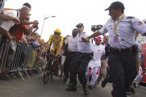 ARCHIVO - En imagen de archivo del sábado 21 de julio de 2012, el  británico Bradley Wiggins viste la camiseta amarilla de líder mientras es escoltado por policías franceses después de cruzar la meta en la etapa 19 del Tour de Francia, en Chartres. Los ciclistas participantes del Tour de Francia de este año estarán protegidos por 23.000 policías, incluidos equipos de fuerzas especiales, en un intento del gobierno de garantizar la seguridad en medio de amenazas de grupos extremistas. (AP Photo/Peter Dejong, File)