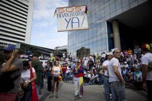 """Un hombre sostiene un cartel que reza """"SOS Revocatorio Ya"""" mientras los manifestantes se reúnen para una marcha por Caracas convocada por la oposición, el jueves 1 de septiembre de 2016. (AP Foto/Ariana Cubillos)"""