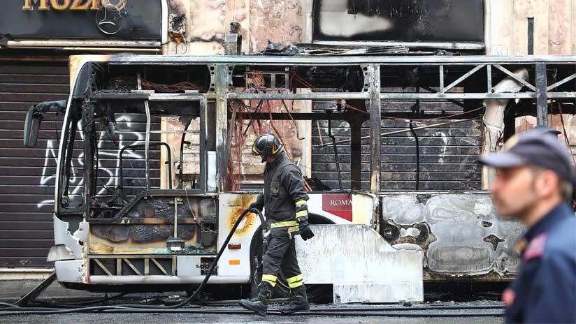 Un bombero camina frente a los restos del autobús incendiado, Roma, Italia, 8 de mayo de 2018.
